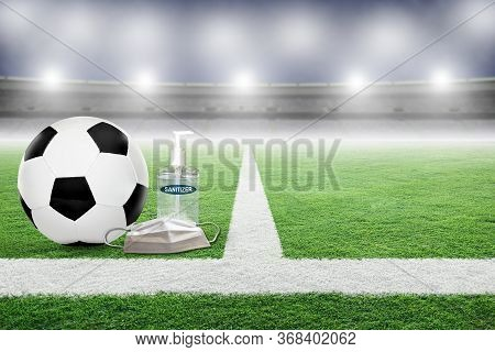 Soccer On Field Of An Empty Stadium With Hand Sanitizer And Medical Face Mask. Concept Of Football P