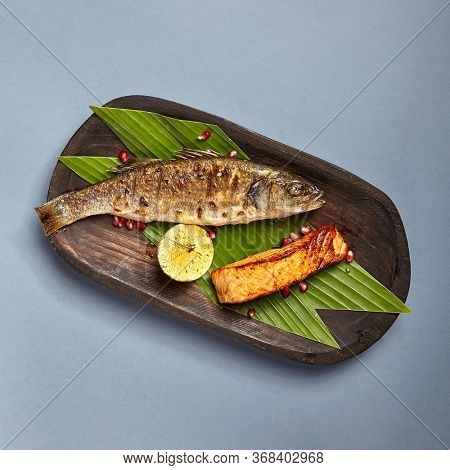 Fish served on wooden rustic plate. Grilled seabass and salmon piece on plant leaves sprinkled with pomegranate seeds. Decorated restaurant meal top view. Fancy seafood assortment dish. Art of cooking