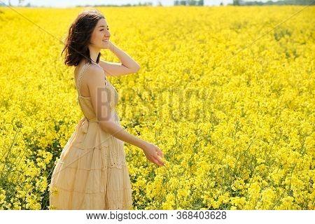Happy Young Girl Walking In Canola Field On Summer Day. Beautiful Woman In Beige Dress Enjoying Natu