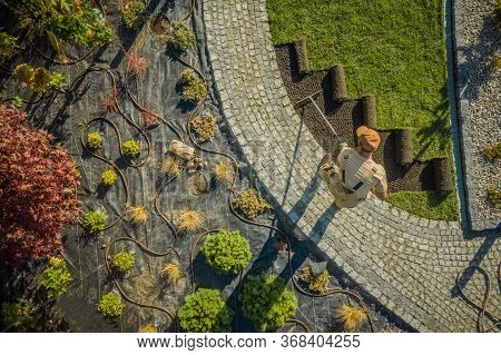 Aerial View Of New Residential Garden Developing By Caucasian Landscaping Worker. Planting Flowers,
