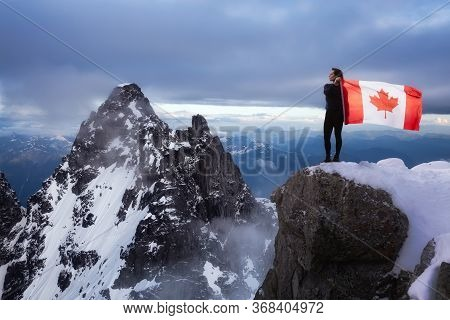 Epic Adventurous Extreme Composite Of Girl Holding A Canadian Flag On Top Of A Mountain. Landscape B