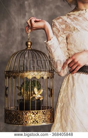 Woman In A White Lace Dress Holding A Golden Cage With Gold Birds And A Cactus. No Face Psychology T