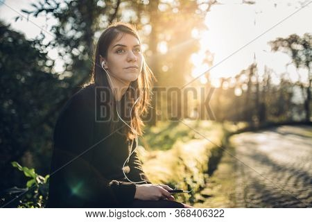 Optimistic Young Woman Listening To Music Podcast Stream Over Headphones,enjoying In Nature At Sunse