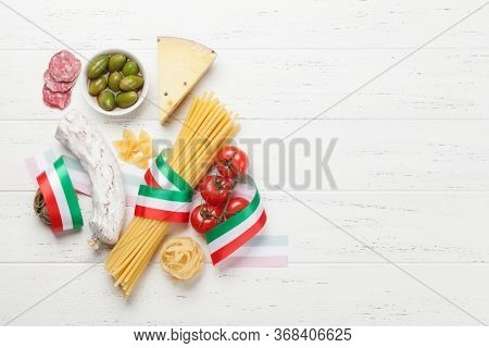 Italian cuisine food ingredients. Pasta, cheese, salami, olives and tomatoes. Top view flat lay on wooden table with copy space