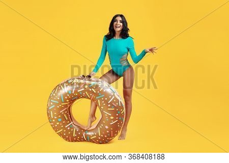 Full Lenght Image Of An Excited Young Fit Woman Dressed In Swimsuit Posing With Inflatable On Orange