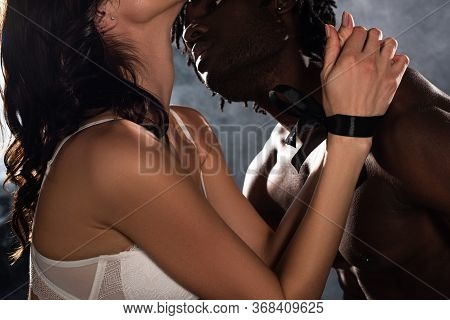 Cropped View Of Seductive African American Man Hugging And Going To Kiss Woman With Bound Hands On B