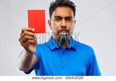 sport, caution, game and football concept - indian referee whistling and showing red penalty card over grey background