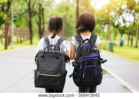 Two Pupils Of Primary School Walking Go To Shool. Two Girl With Bags Behind The Back. Warm Day Of Fa