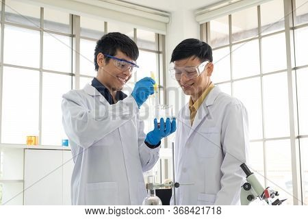 Science, Chemistry, Technology, Biology And Laboratory Concept - Asian Senior Scientist And Asian Ju