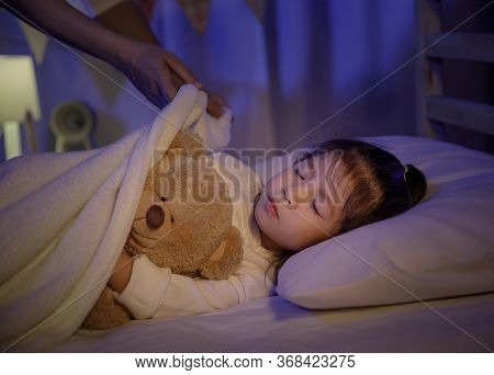 Mother Putting Blanket On And Stroking Head For Her Little Girl Daughter On Bed In A Dark Bedroom At