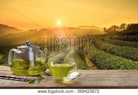 Green Tea Cup And Glass Jugs Or Jars. With And Green Tea Leaf Sacking On The Wooden Table And The Te