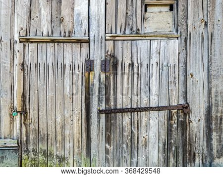 Detailed View Of An Old Wooden Barn Wall And Closed Doors With Rusty Padlocks