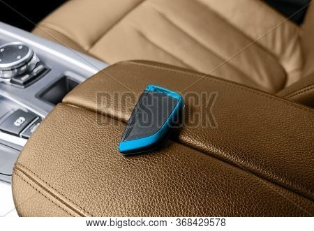 Closeup Inside Vehicle Of Wireless Key Ignition. Start Engine Key. Car Key Remote In Brown Perforate