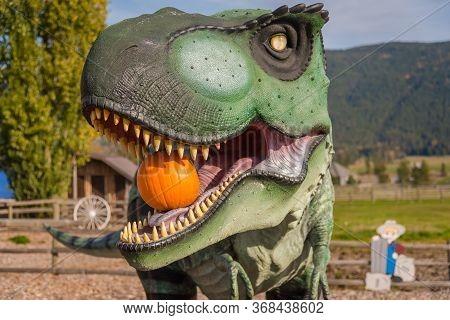 Armstrong, British Columbia/canada - October 23, 2016: Tyrannosaurus Rex Statue Holding Pumpkin In I