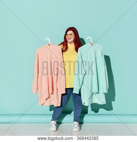Young Smiling Plus Size Woman In Jeans Hoodie And Sneakers Holds Chooses Between Blue And Pink Hoodi