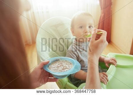 Mother Or Babysitter Feed Hungry Kid Sitting In Highchair With Baby Food From Spoon. Innocent Child