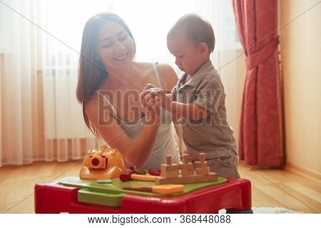Smiling Happy Young Caucasian Mother Playing With Son Indoor. Caring Nanny Babysitter Teach Child Bo