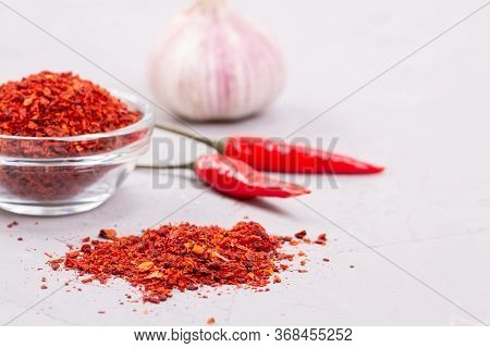 Harissa Seasoning In A Glass Plate, Fresh Garlic And Two Chili Peppers