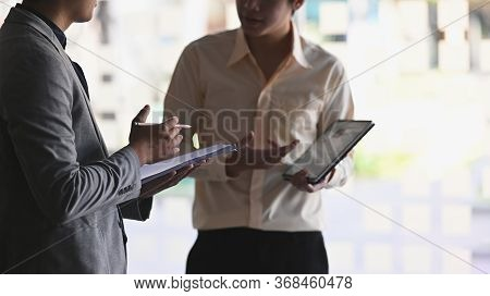 Closeup Investment Consultant Standing At Modern Office And Consulting With Young Professional Man.