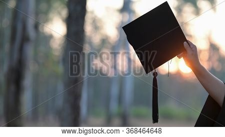 Graduate Woman Hand Holding The Graduation Cap In Her Hand Over Blurred Forest Background.  Graduati