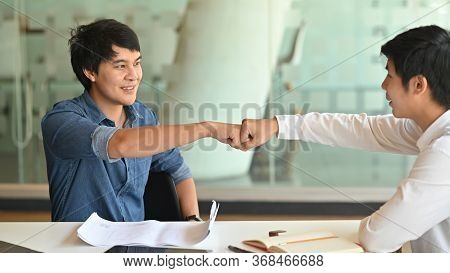 Fist-bump Or Knuckle-bump Of Businessmen After Finished Discussing About Project Problem With The Mo