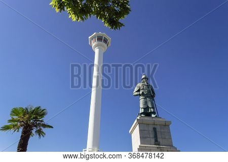Busan, South Korea, September 14, 2019: View Of Busan Tower With Statue Of Yi Sun-sin In Front Of It