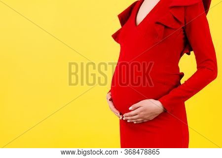 Cropped Image Of Pregnant Woman Wearing Red Dress. Young Mother Is Hugging Her Belly Expecting A Bab