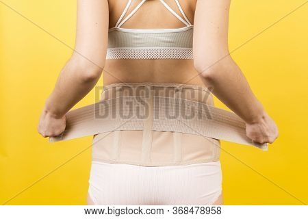 Back View Of Pregnant Woman In Underwear Dressing Orthopedic Corset To Make The Backache Go Away At
