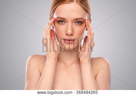 Beautiful Young Female With Freckled Skin Touching Temples And Looking At Camera While Suffering Fro
