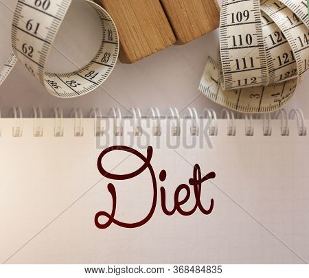 Diet Plan Concept. Measuring Tape And Paper Notebook With Inscription Diet Plan On Blue Wooden Backg