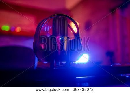 Condenser Microphone And A Headphone On The Table And Light Back