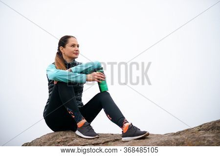 Beautiful Smiling Woman Resting and Drinking Water after Trail Running Outdoor. Workout Exercise at Cold Autumn Evening. Sport and Healthy Active Lifesyle Concept.
