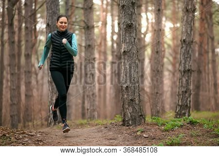 Beautiful Smiling Woman Running on the Forest Trail at Cold Autumn Evening. Sport and Active Lifestyle Concept.