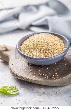 Raw  White Quinoa Seeds (lat. Chenopodium Quinoa) On  Plate With Wooden Spoon. Raw  Black Quinoa See