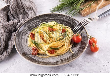 Spaghetti With Agretti, A Spring Vegetable From Italy, And Sun Dried Tomatoes With Fork And Ingredie