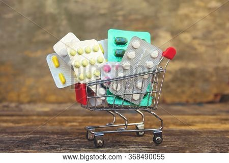 Shopping Cart With Pills On Wooden Background. Сoncept Of Buying Medicines.