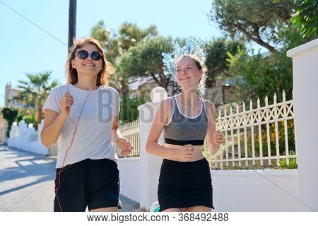 Active Athletic Family, Mother And Teenage Daughter Running Together On An Outdoor Road. Healthy Lif