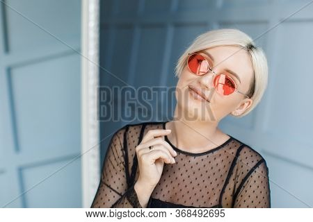 Stylish Blond Woman With Short Hair Cut With Trendy Red Sun Glasses. Beauty Blond Woman With Blue Ey
