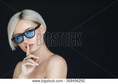Blond Woman With Short Hair Cut In Trendy Sun Glasses With Black Background. Beauty Blond Girl Portr
