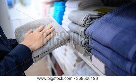 Buying New Towel Concept. Male Hand Customer Choosing Gray (grey) Towel Form Display Rack In Cloth S