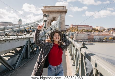 Carefree Woman In Casual Red Sweater Enjoying Life And Posing On City Background. Stunning Female Mo