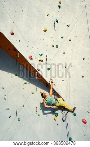 Sports Woman Climber Practicing Rock Climbing On Artificial Rock Wall In Climbing Gym, Resting And C