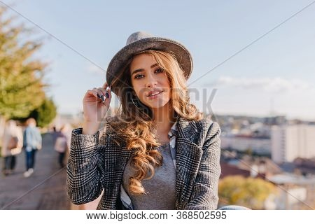 Interested Blue-eyed Woman In Trendy Hat Posing During Morning Walk. Portrait Of Attractive Curly Fe