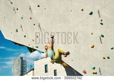Young Woman Rock Climber Climbing On Artificial Rock Wall In Outside Climbing Gym. Sports Woman Work