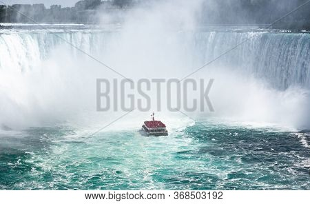 Niagara Falls, Canada - July 2019. A Boat With Tourists At The Bottom Of Horseshoe Waterfall.