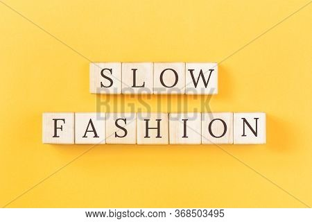 Slow Fashion Text On Building Blocks On Plain Yellow Background. Sustainable Approach To Manufacturi