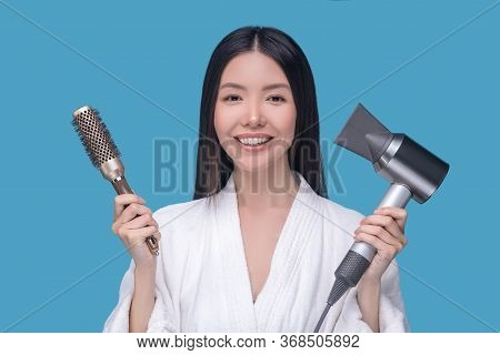 Brunette Young Asian Woman Holding A Brush And A Hair Dryer