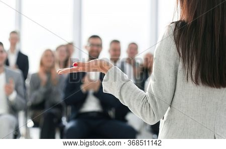 young businesswoman finishing her speech to the applause of the business team.