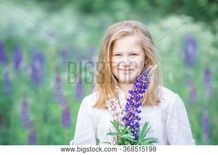 Portrait Of A Fair-haired 10-year-old Girl In A Field With Lilac Flowers. Smiling, Holding Lilac Flo