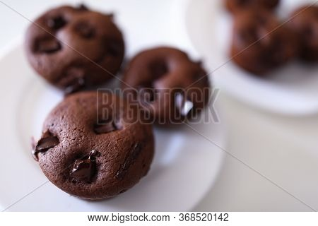 Close-up Of Delicious Chocolate Muffins With Crispy Top Served On White Plate. Homemade Tasty Cupcak